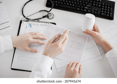 healthcare, hospital and medical concept - two doctors prescribing medication