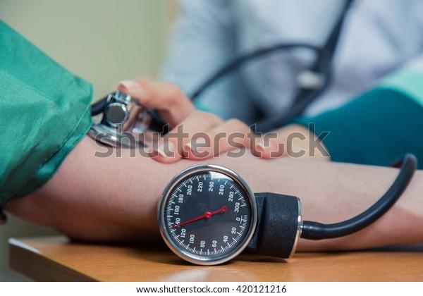 healthcare, hospital medicine concept - doctor and patient measuring blood pressure