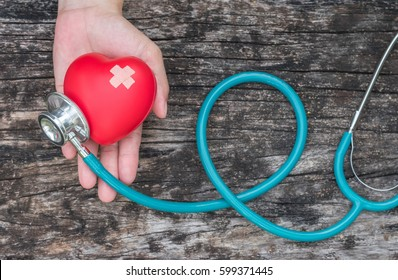 Healthcare insurance and World heart health day concept with red heart on woman's hands support with medical doctor's stethoscope