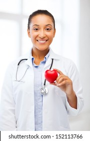 healthcare, medical and cardiology concept - african female doctor with heart