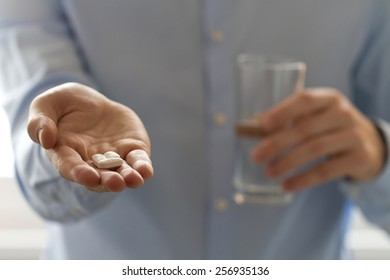 Healthcare and medical concept. Close-up view of man holding pills in one hand and glass of water in the another hand