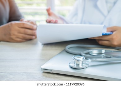 Healthcare medical concept. Doctor Explain and recommed to patient listening receiving prescriptions medicine with prescription clipboard record paper in doctor's office. Focus stethoscope computer