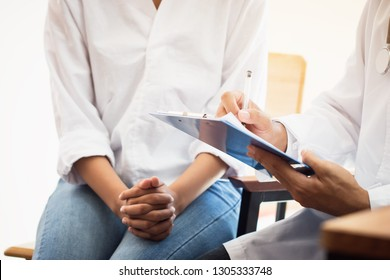 Healthcare medical concept : Doctor / psychiatrist consulting gynecological female illness, writing prescription clipboard record information,patient listening receiving in medical clinic hospital.