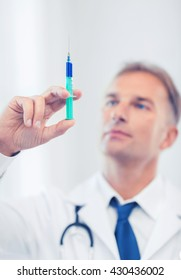 healthcare and medical concept - male doctor holding syringe with injection