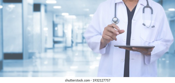 Healthcare and medical concept. Male medicine doctor with stehoscope using digital tablet and hospital background