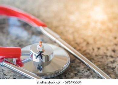 Healthcare and medical concept. Woman miniature figure sitting and reading a book on stethoscope
