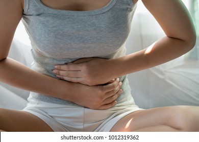 Healthcare medical or daily life concept : Close up stomach of young lady have a stomachache or menstruation pain sitting on her bed.