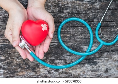 Healthcare medical insurance business and world heart health day concept with red heart and bandage (band-aid) on woman's hands support with doctor's stethoscope
