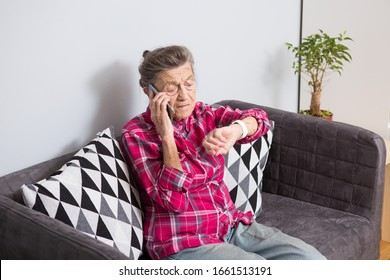 Healthcare, medical, omnichannel and technology concept. Old person using smart watch and while talking to someone on the phone. Old woman pensioner uses Fitness Tracker. Elderly Woman Phone Calling.