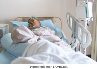 Healthcare and medical patient concept, Elder Asian people sick sitting alone on bed in hospital with medical drip intravenous needle, give salt water when her get well after treatment or surgery