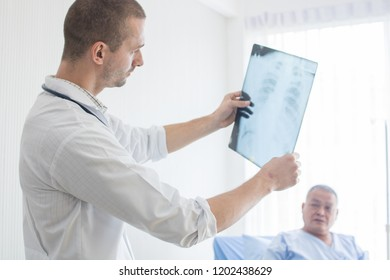 Healthcare and medical people concept, doctor looking on X-ray film of old patient and checking problem of spine bone