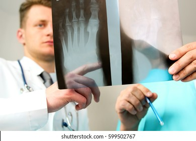 healthcare, medical and radiology concept -  Male doctors looking at x-ray of foot