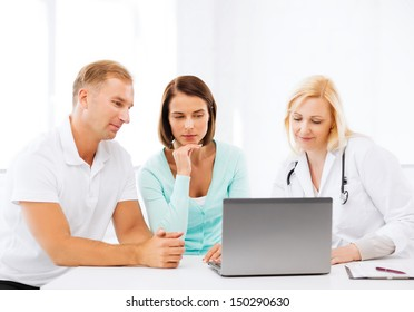 healthcare, medical and technology concept - doctor with patients looking at laptop