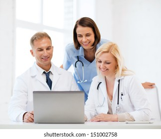 healthcare, medical and technology concept - group of doctors looking at laptop