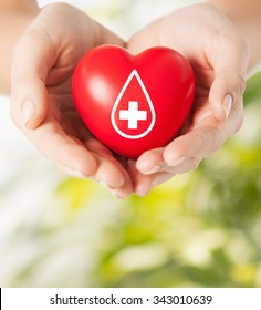 healthcare, medicine and blood donation concept - female hands holding red heart with donor sign over green natural background