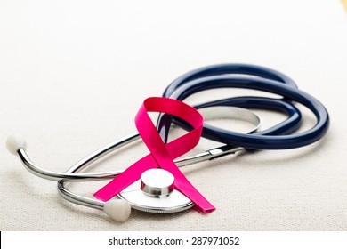 Healthcare, medicine and breast cancer awareness concept. Closeup pink ribbon on stethoscope.