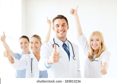 healthcare and medicine concept - attractive male doctor in front of medical group in hospital showing thumbs up