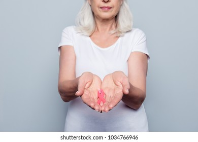 Healthcare and medicine concept -  blonde fighter woman holding in hands pink breast cancer awareness ribbon, donate, tumor, organization, campaign, faith, gray background