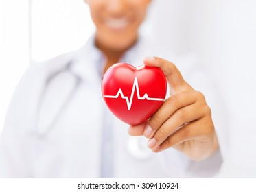 healthcare and medicine concept - female african american doctor holding red heart with ecg line