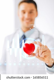 healthcare and medicine concept - male doctor with heart and cardiogram