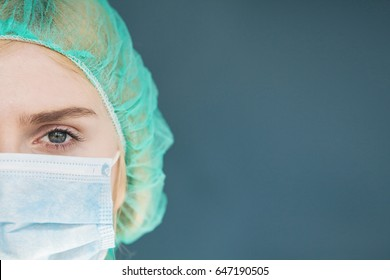 Healthcare, medicine concept: Portrait of female surgeon, medical mask is protection face, close up. Doctor looks at camera.
