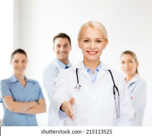 healthcare and medicine concept - smiling female doctor with stethoscope ready to shake hands