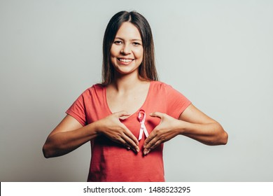 Healthcare and medicine concept - woman in t-shirt with pink breast cancer awareness ribbon