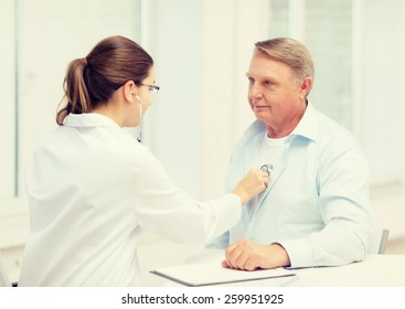 healthcare, medicine and elderly concept - female doctor or nurse with old man listening to heart beat