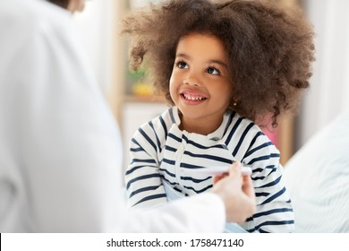 healthcare, medicine and people concept - doctor showing thermometer to happy smiling sick little african american girl in bed at home