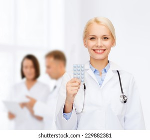healthcare, medicine and pharmacy concept - smiling female doctor and with pills and stethoscope