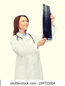 healthcare, medicine and radiology concept - smiling female doctor with stethoscope looking at x-ray