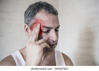 healthcare, pain, stress, age and people concept -mature man suffering from headache at home. Man touching forehead . Negative human emotion facial expression feeling