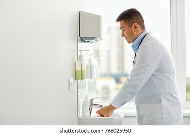healthcare, people and medicine concept - doctor washing hands at medical clinic sink