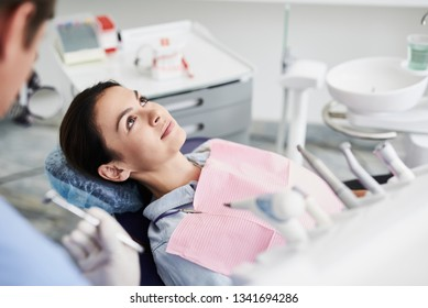 Healthcare. Portrait of charming girl lying in dentist chair and looking up with serene expression
