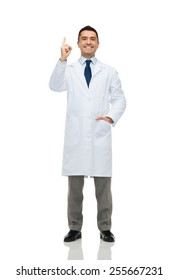 healthcare, profession, people and medicine concept - smiling male doctor in white coat pointing finger up