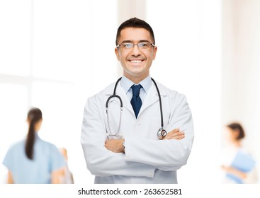 healthcare, profession, people and medicine concept - smiling male doctor in white coat over group of medics at hospital background