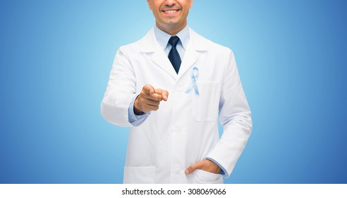 healthcare, profession, people and medicine concept - close up of smiling male doctor in white coat with sky blue prostate cancer awareness ribbon pointing finger to you