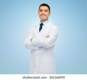 healthcare, profession, people and medicine concept - smiling male doctor in white coat over blue background