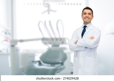 healthcare, profession, stomatology and medicine concept - smiling male middle aged dentist over medical office background