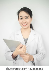 healthcare, profession, stomatology and medicine concept:smiling woman young aged doctor hand holding blur tablet shows a list of patients. over wall in medical office background