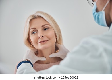 Healthcare professional in a face mask and sterile gloves palpating the female patient thyroid gland