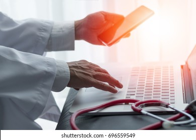 Healthcare professional medical doctor using notebook computer and smartphone for consult patient via online: Physician working tele-consultation: Hospital e-healthcare professionalism concept