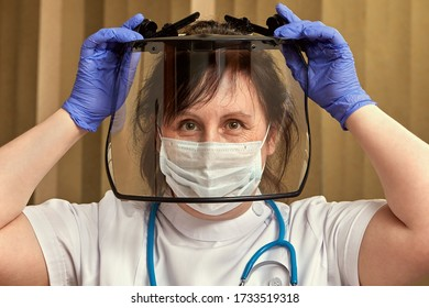 Healthcare professional in medical protective mask, gloves and glasses is putting on surgical equipment to protect herself  during the coronavirus pandemic and home isolation.