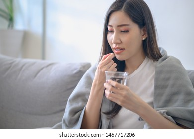 Healthcare or sickness concept : Beautiful young Asian woman taking a medicine because she caught a cold or sick with fever.