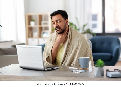healthcare, technology and people concept - sick indian man in blanket with sore throat having video call on laptop computer at home