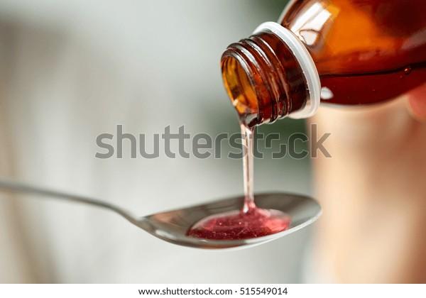 concepto de asistencia sanitaria, tratamiento y medicina - botella de medicación o jarabe antipirético y cuchara