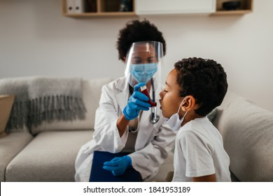 Healthcare worker at home visit. Female doctor is helping little boy to use asthma pump