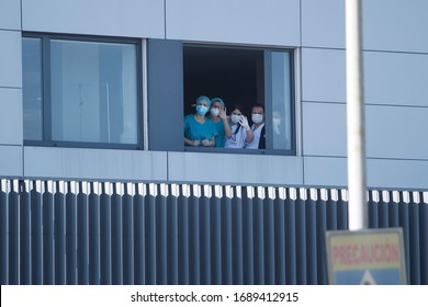 Healthcare workers dealing with the new coronavirus crisis look through the windows of the University Hospital in Coruna, northwestern Spain, on March 26, 2020