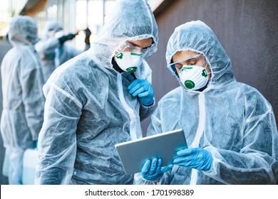 Mitarbeiter im Gesundheitswesen, die gefährliche Anzüge tragen, arbeiten zusammen, um einen Ausbruch zu bekämpfen