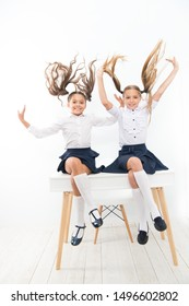 Healthier hair from root to tip. Adorable little girls with flying hair sitting on desk. Cute small children with long hair ponytails wearing school uniform. Luxurious hair extensions.